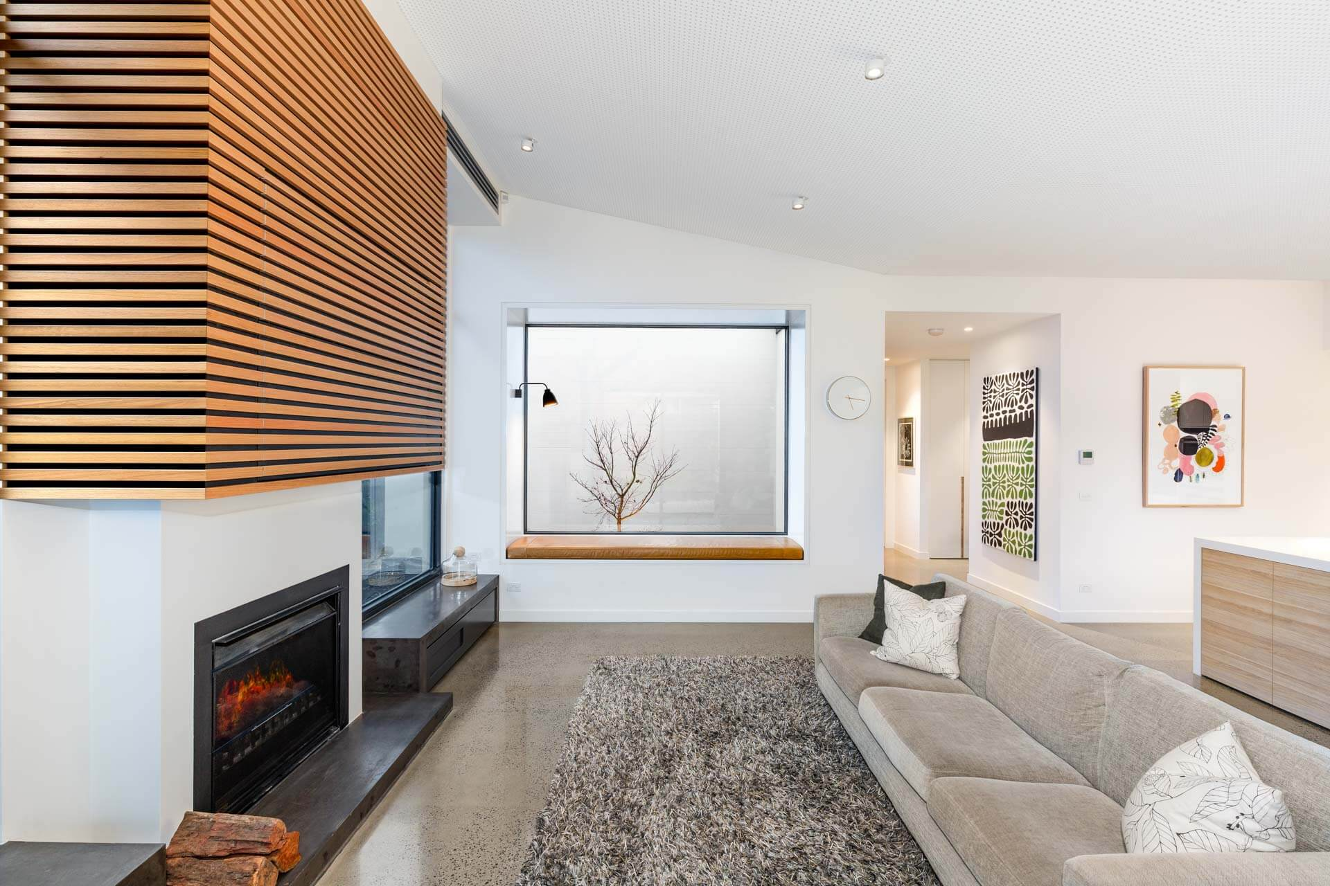 Renovated custom designed lounge area with sofa chair and fire place feature wall and polished concrete floor and perforated ceiling Architectural Photography Roger Thompson Photography