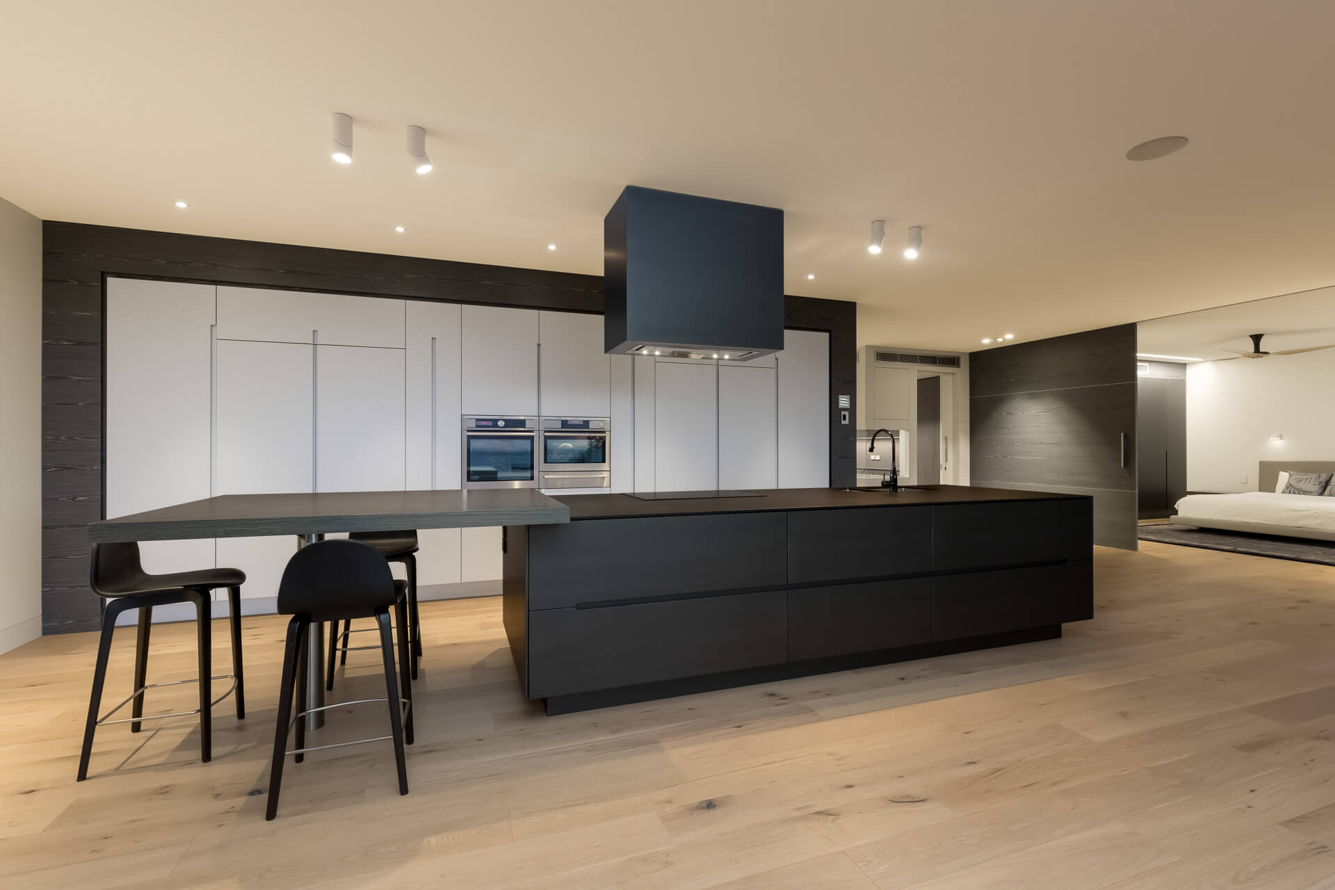 Custom design kitchen with grey cabinetry and dark brown breakfast bar kitchen island on timber flooring looking in to master bedroom with oversized sliding door in Brighton bayside melbourne Architectural Photography Roger Thompson Photography