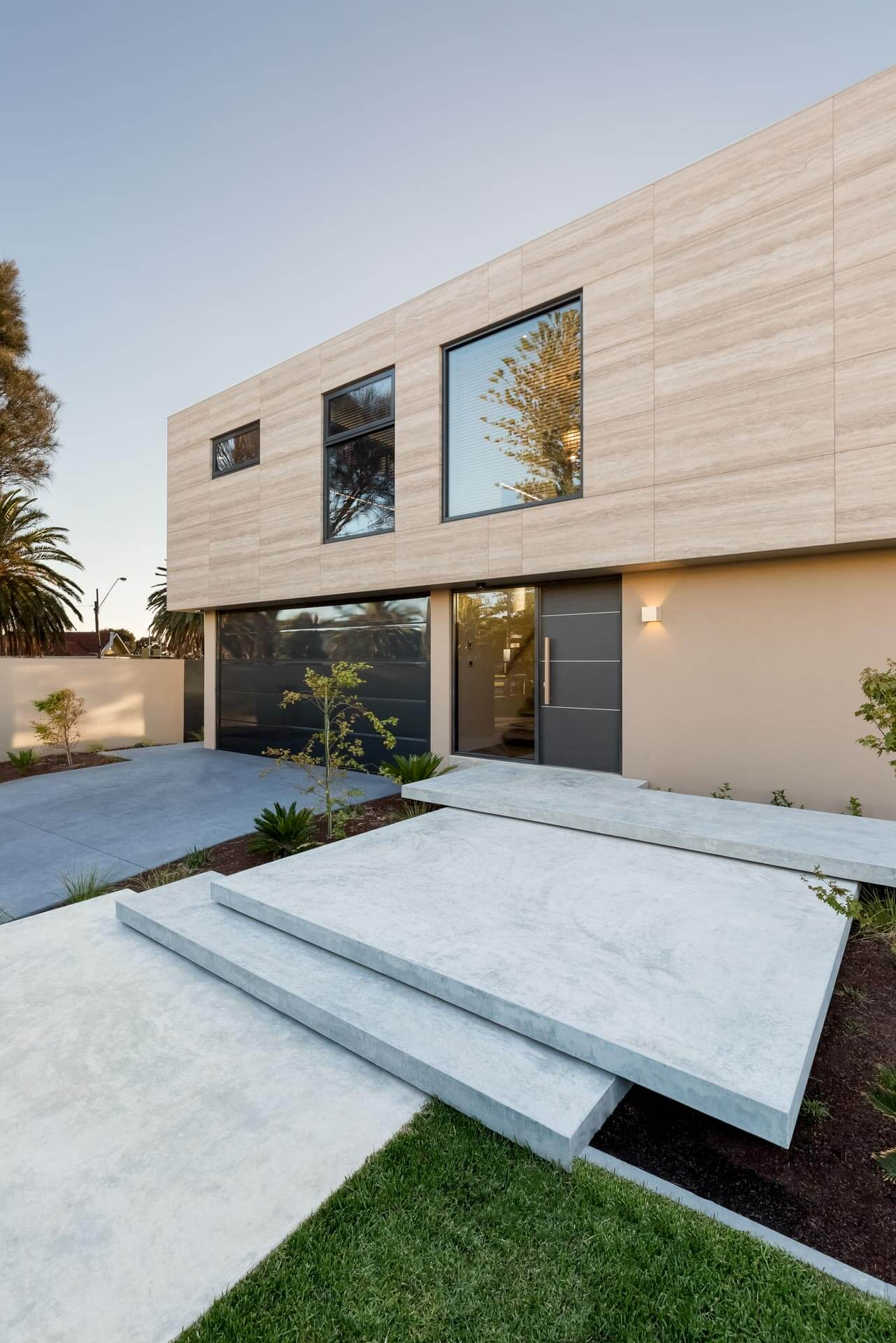 afternoon photo of Custom designed contemporary renovation front door facade area with floating concrete steps and garden and driveway in Brighton bayside home in melbourne by Roger Thompson Photography