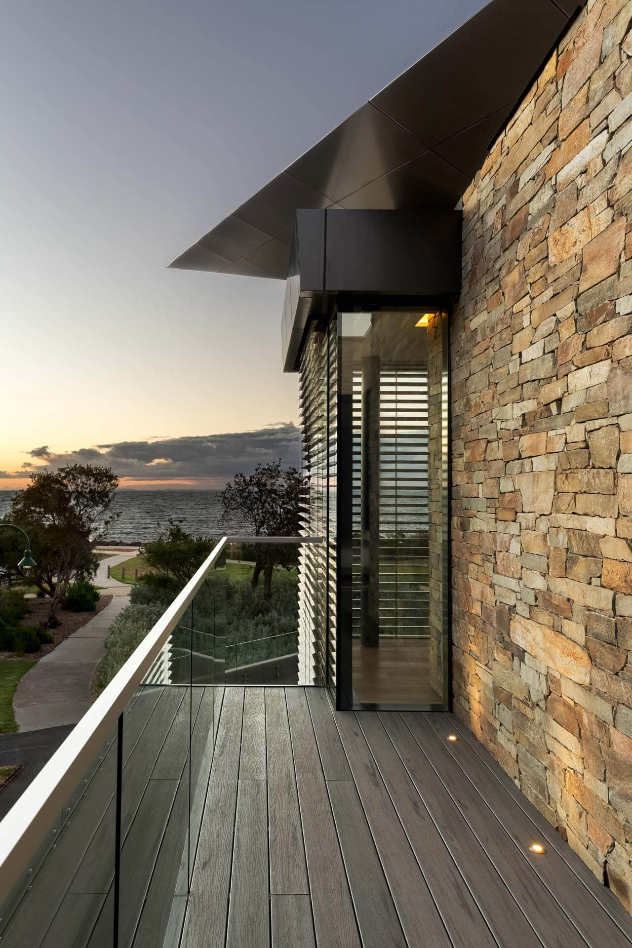 dusk photograph of Master bedroom private deck looking out to Port Phillip Bay and walking path in Brighton bayside home renovation in melbourne