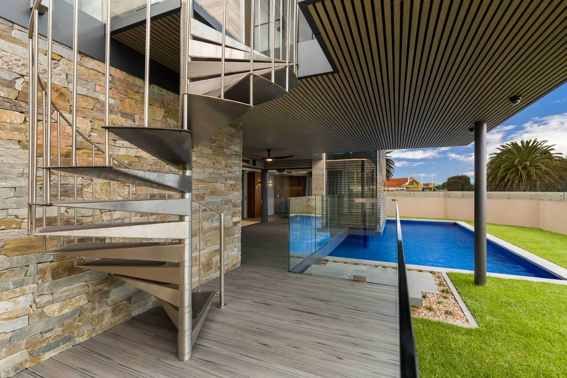 photograph of alfresco deck area with pool and spiral stainless steel staircase and grass garden in Brighton bayside home renovation in melbourne