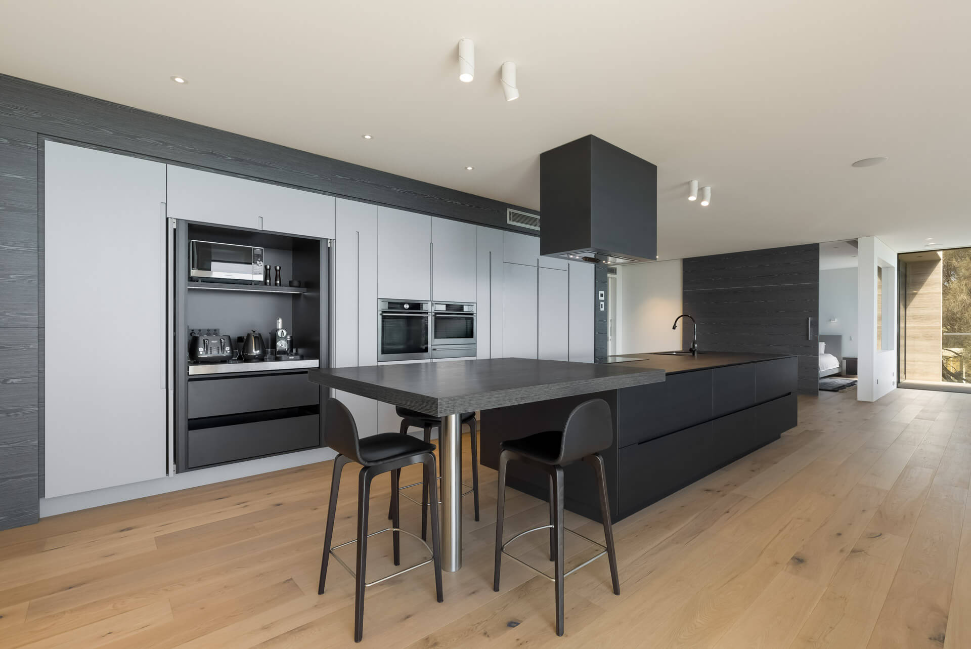 Designer grey and black colour kitchen cabinetry island bench and rangehood with breakfast bar with master bedroom photograph in Brighton bayside home renovation in melbourne