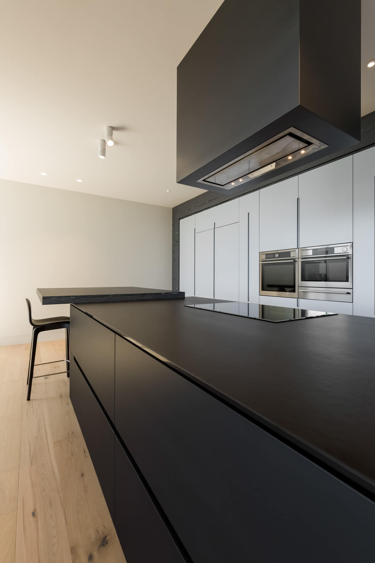 Designer grey and black colour kitchen cabinetry island bench and rangehood with breakfast bar photograph of Brighton bayside home renovation in melbourne