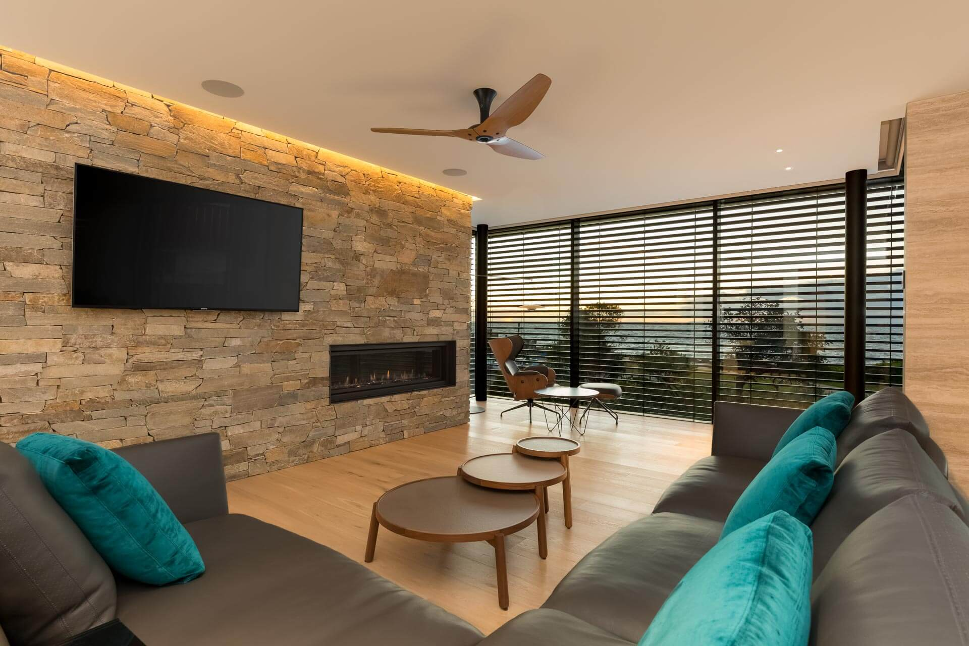 Custom design lounge area with couch cushions stone wall tv and gas fireplace with sunset overlooking Brighton bayside melbourne Architectural Photography Roger Thompson Photography