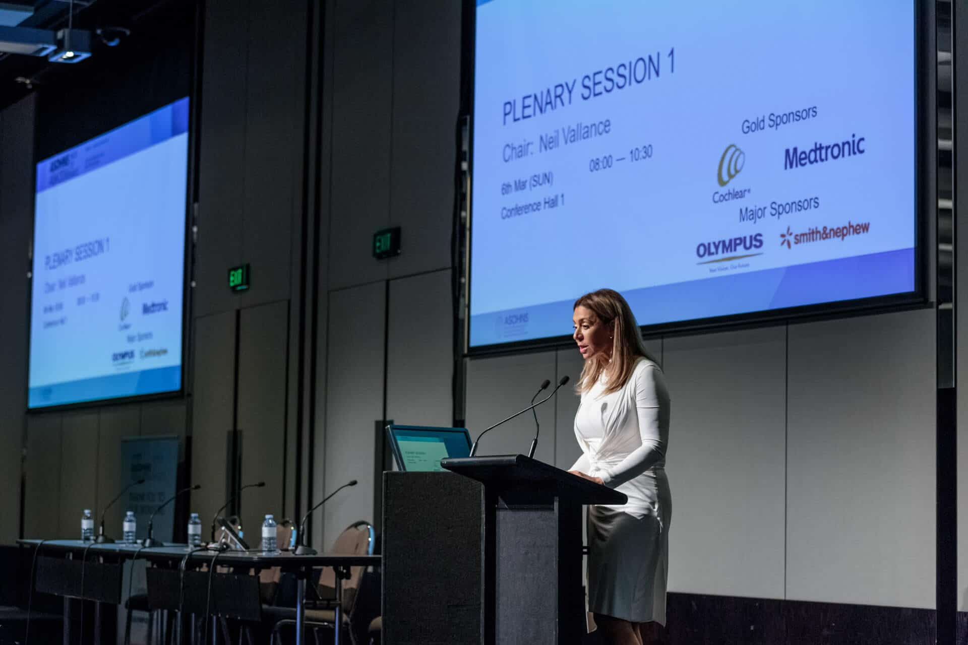 important speaker in front of two large projector screens event photograph from asohns crown conference event in melbourne