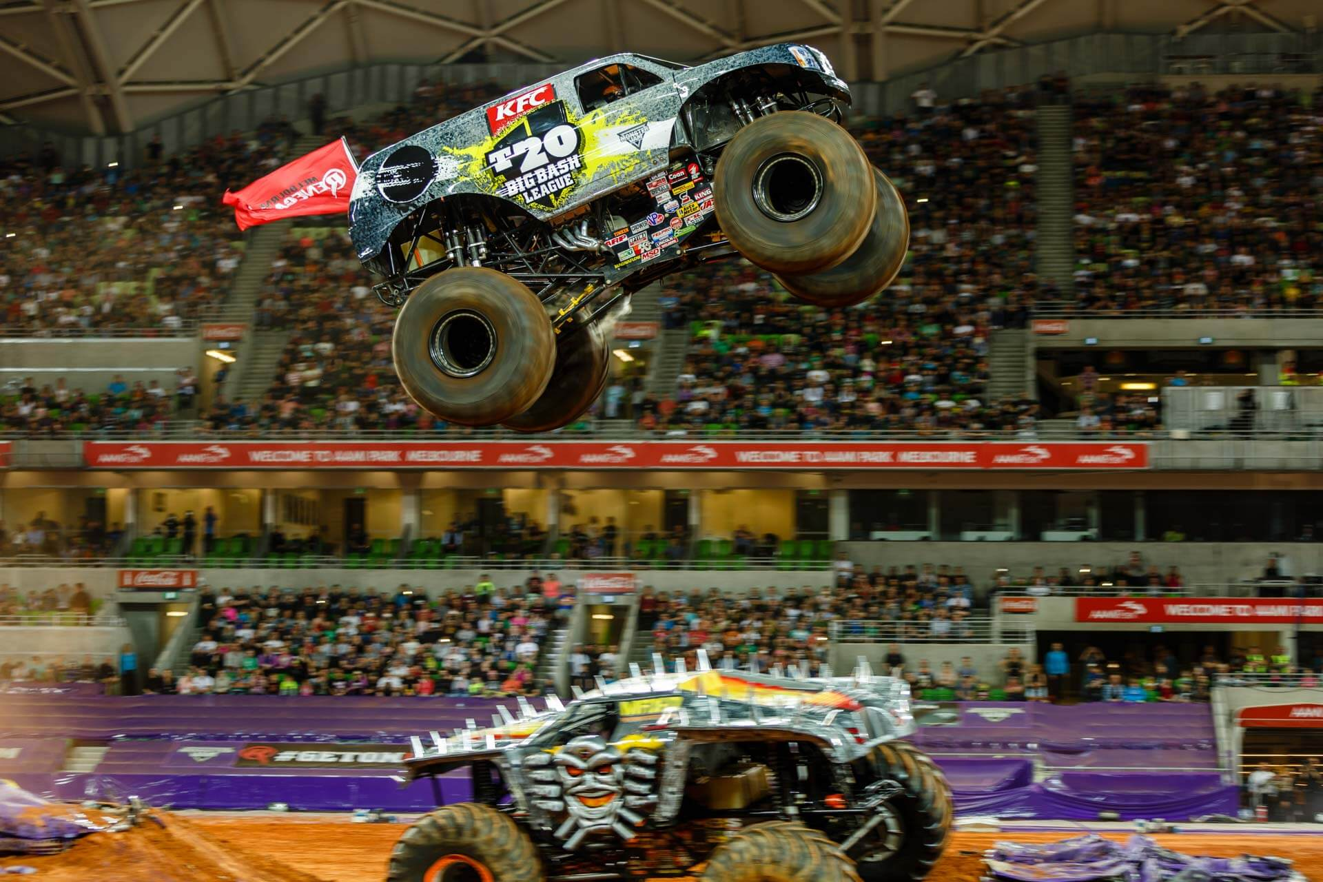 Monster Jam monster truck flying through the air after a big jump jumping over max-d monster truck at ammi park stadium melbourne