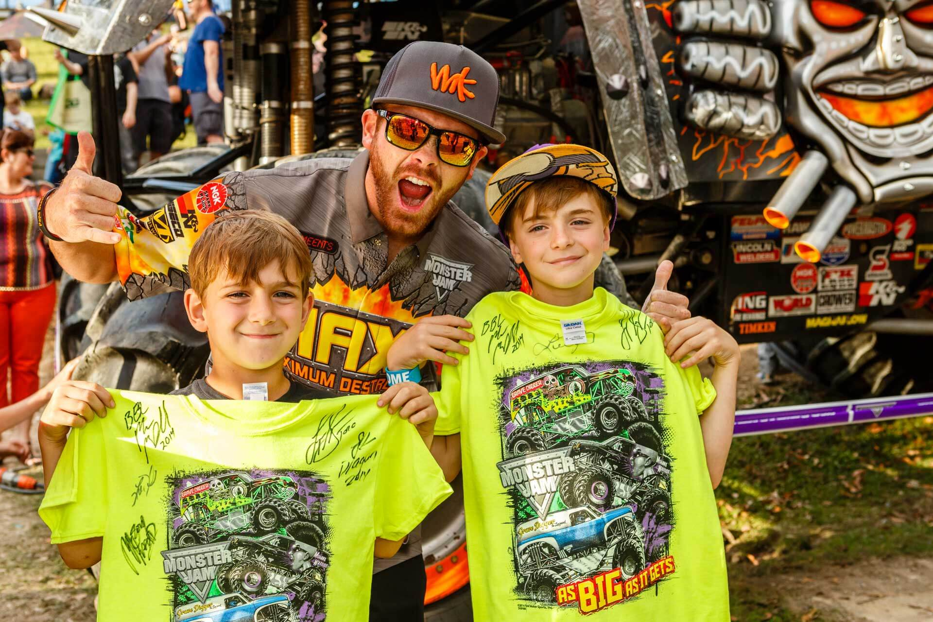 monster jam max-d driver posing with two boys holding up monster jam autographed bright yellow t-shirts in front of max-d monster truck