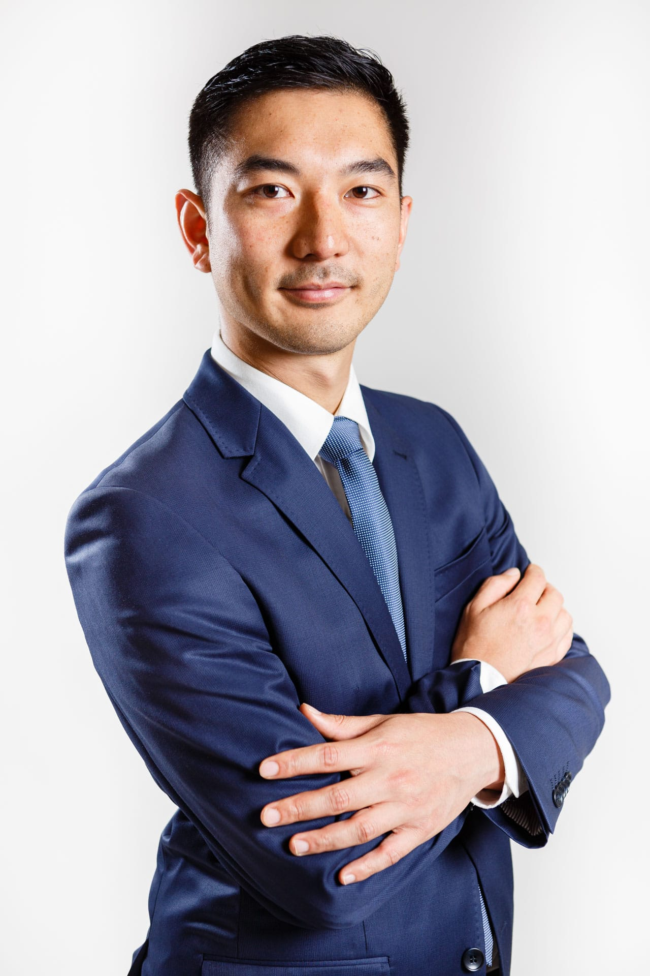 professional corporate portrait head shot of real estate agent man smiling dressed in dark blue suit white shirt and mid blue ties