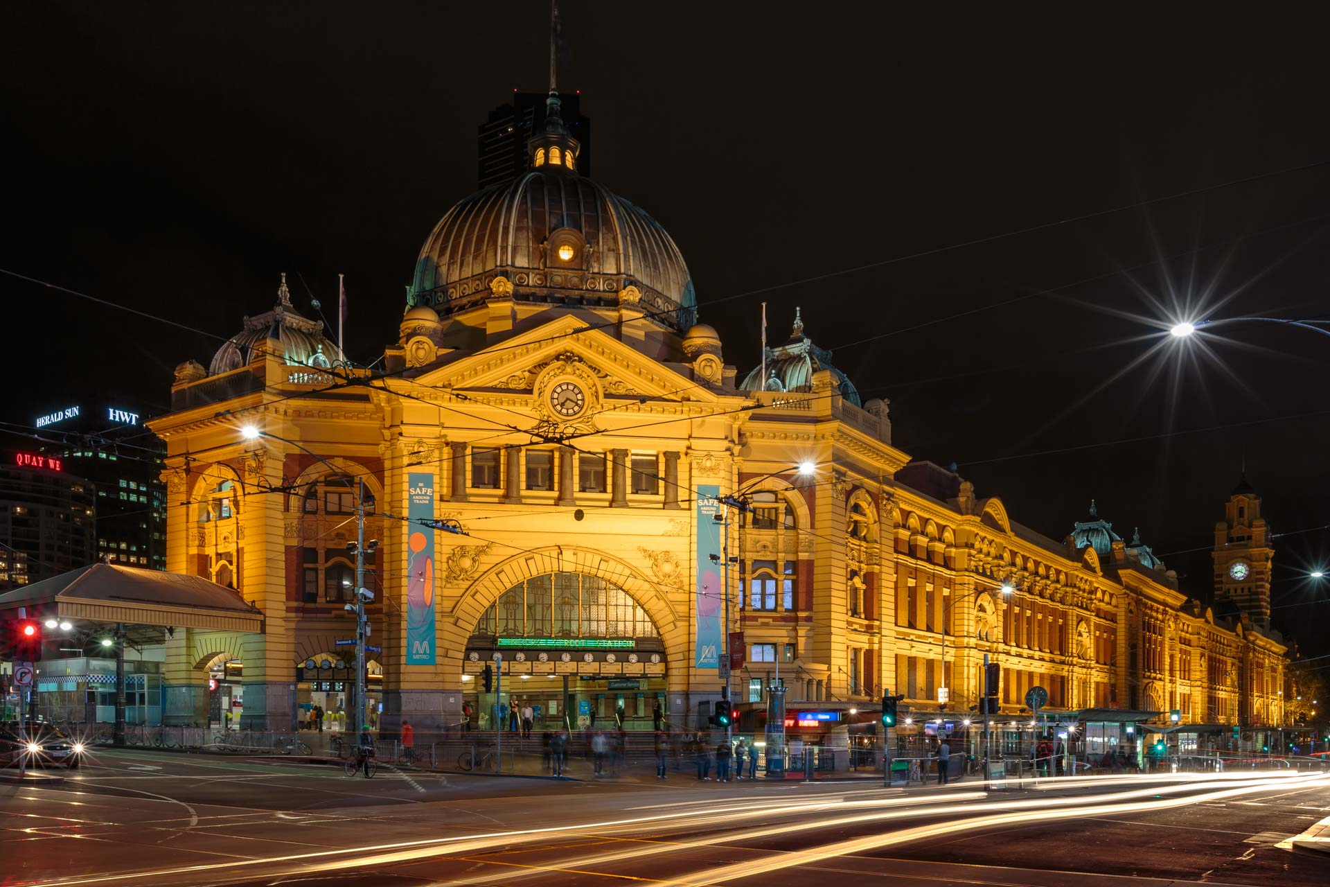flinders street station illuminated building in cityscape melbourne long exposure photographed at night with car headlights blurred passing by