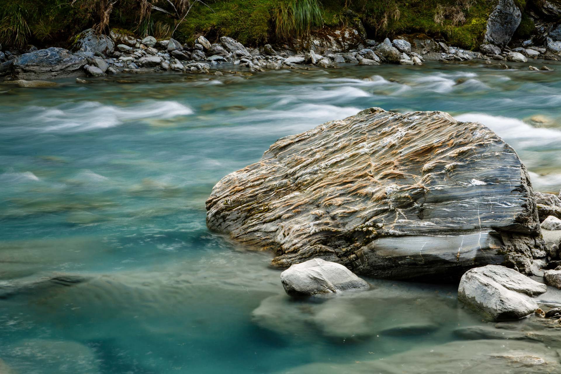 queenstown landscape river wth large rock photographed with slow shutter speed to blur water flowing in river