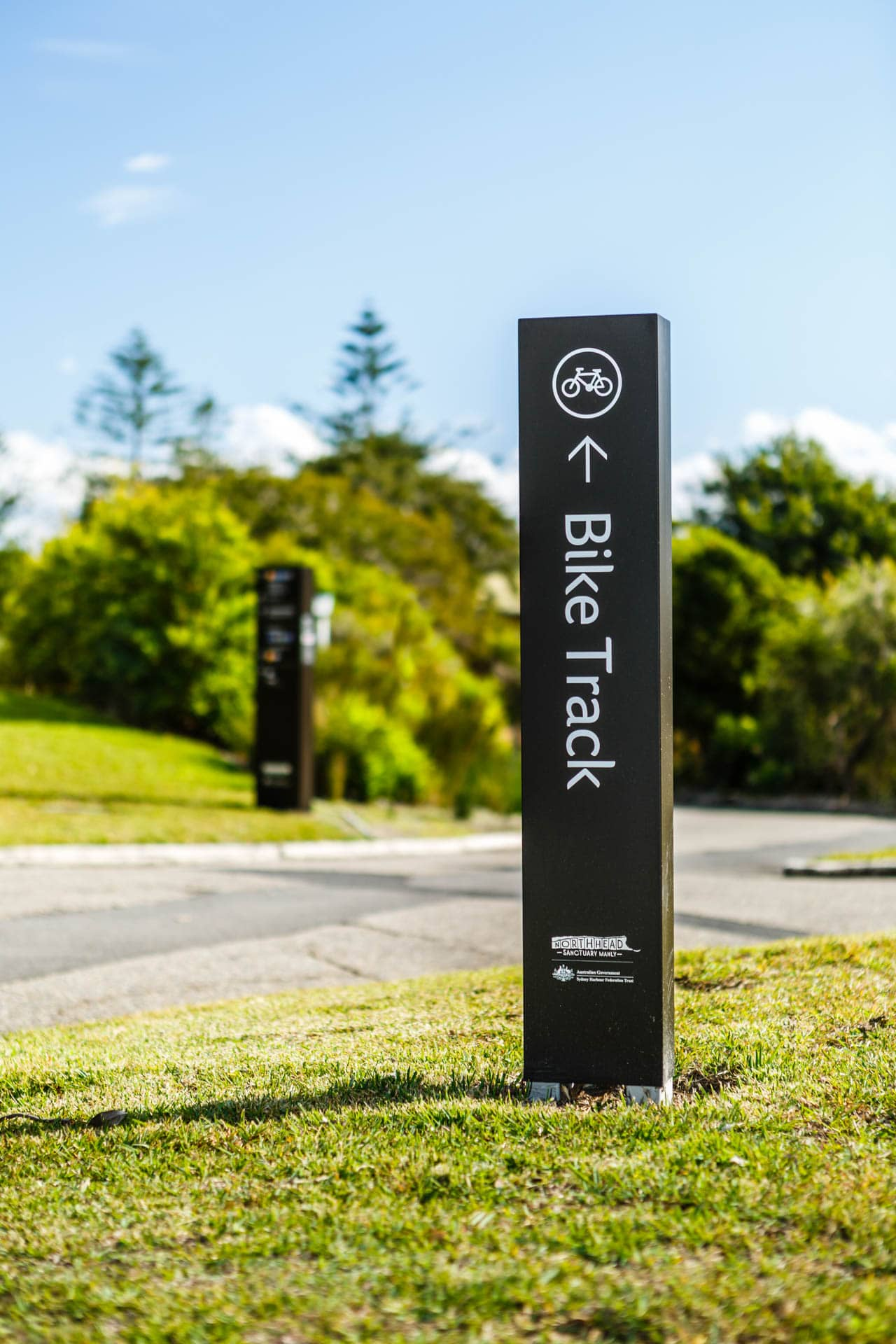 black metal wayfinding directional bike track sign photo installed in to sydney north heads sanctuary park area roger thompson photography