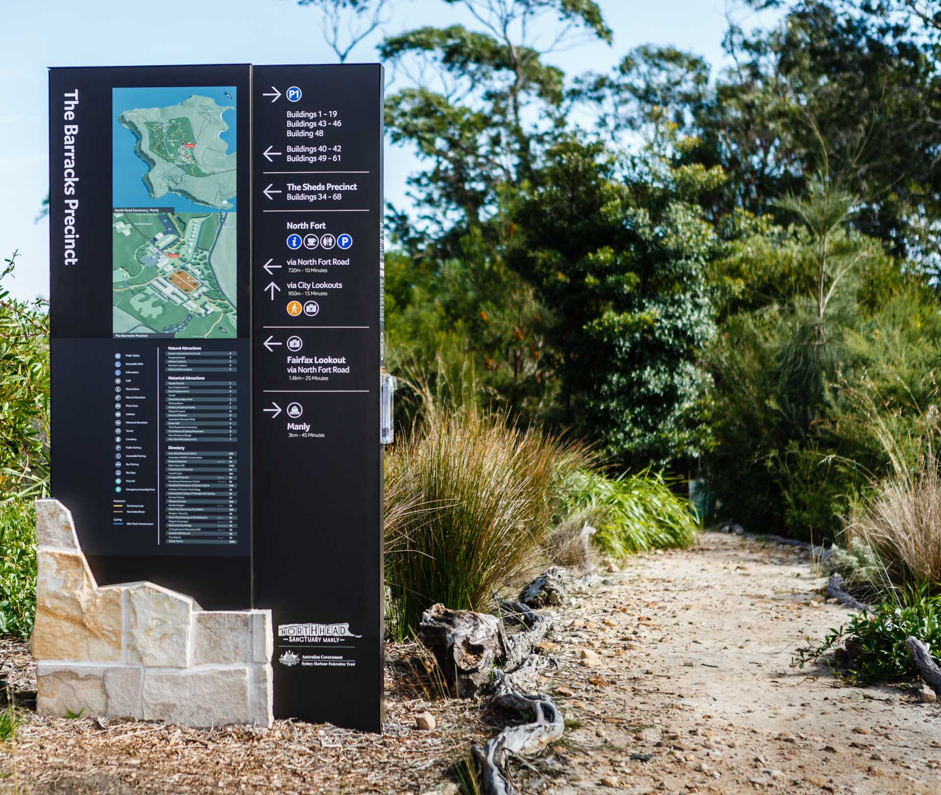black metal and stone wayfinding sign with map image installed in to sydney north heads sanctuary park area