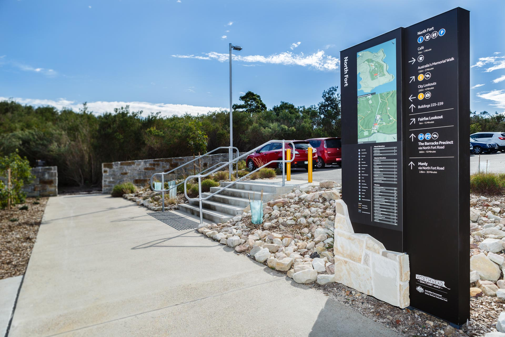 black metal and stone wayfinding sign with map image installed near car park area within sydney north heads sanctuary park area