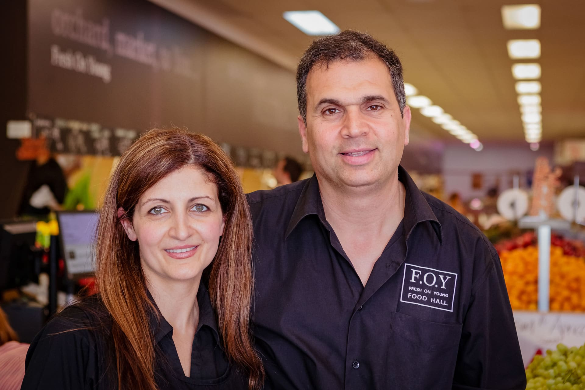 husband and wife business owners portrait photograph at their fresh food business fresh on young store with in store in the background behind them