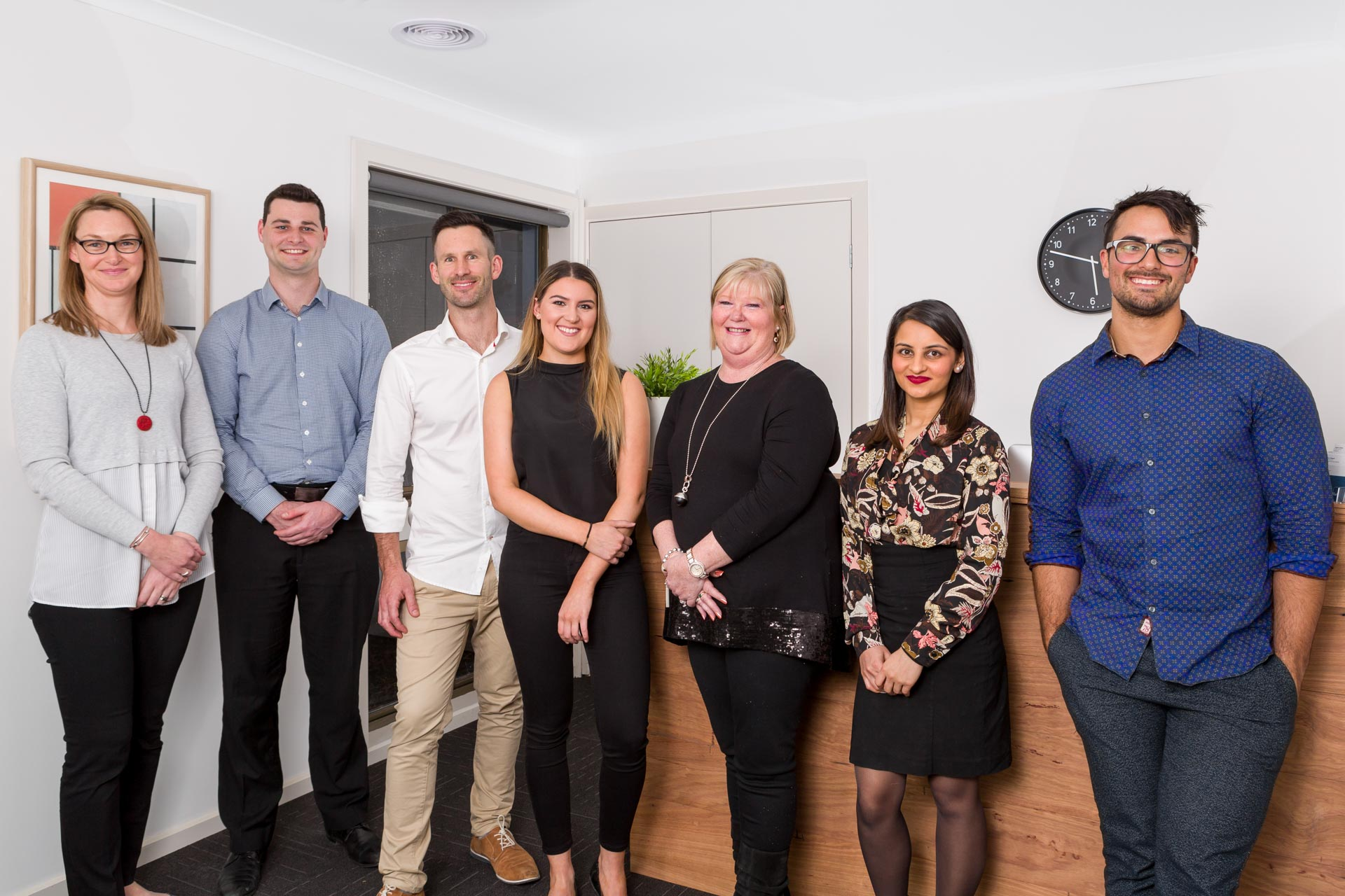 group workplace photo of staff and director all standing in reception area smiling