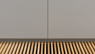 - hydronic heating grill close up product photograph with timber grate matching timber flooring positioned below grey cabinetry