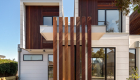 exterior photography of West Footscray townhouse new development, architectural design, iron bark wood features, white facade, roger thompson photography, blue sky,