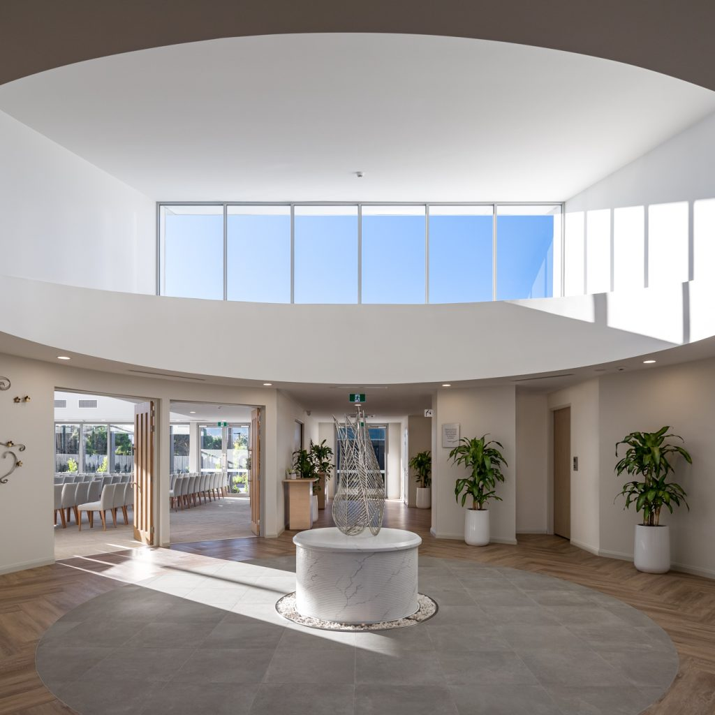 Le Pine and white lady funeral home circular grand hallway with water feature sculpture looking in to chapel internal photo by Roger Thompson Photography Melbourne