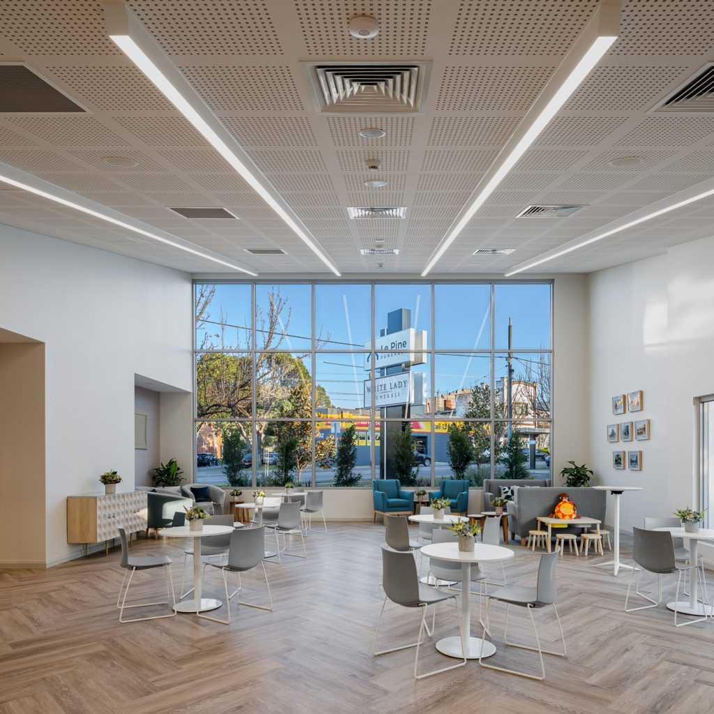 Le Pine and white lady funeral home communal gathering area internal photo showing seating and large bright front windows by Roger Thompson Photography Melbourne