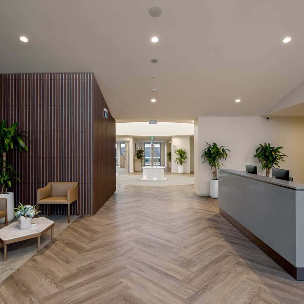 Le Pine and white lady funeral home entry foyer reception area photo looking though to circular grand hallway with water feature sculpture by Roger Thompson Photography Melbourne